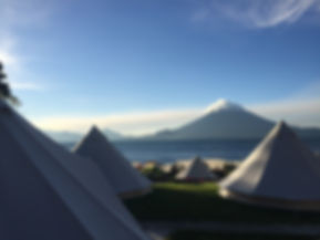 glamping tents at Free Cerveza hostel on Lake Atitlan with volcan fuego in the distance