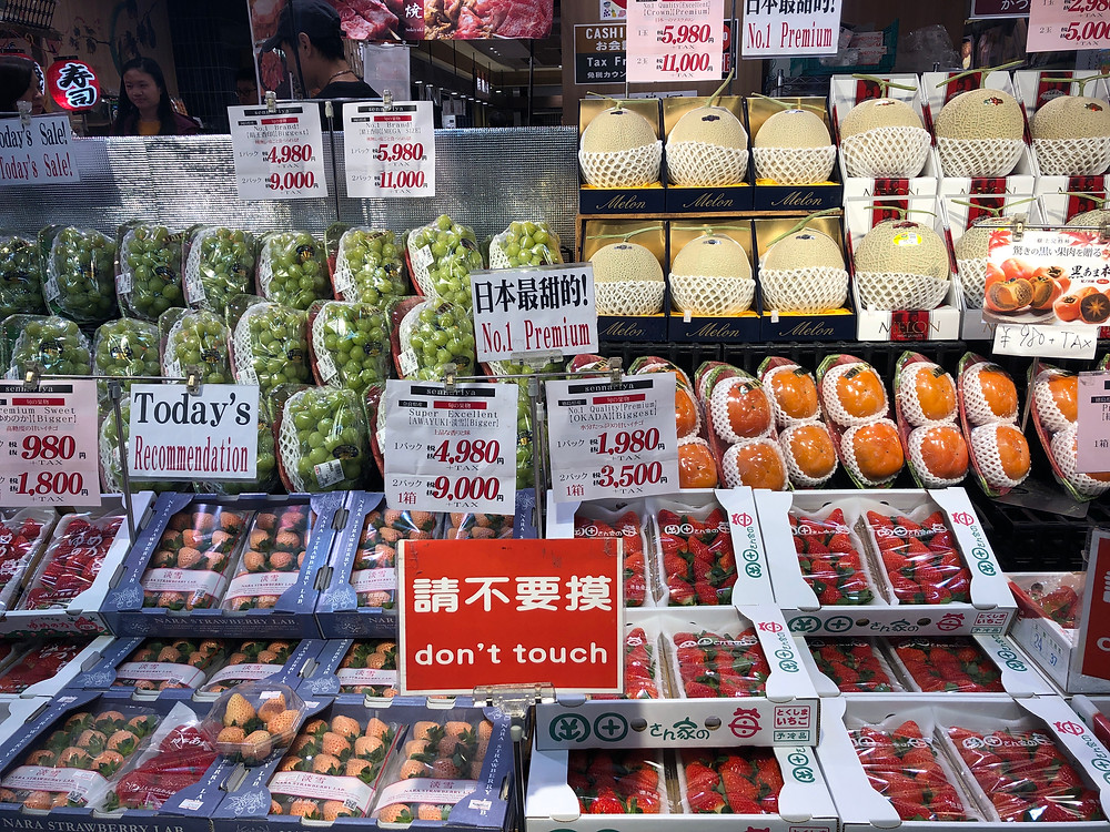 A fruit stand in Kyoto's public market in Japan with melons, grapes, strawberries and persimmons