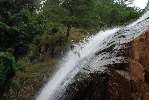 a traveler doing the canyoning tour climbing down a waterfall in Dalat Vietnam