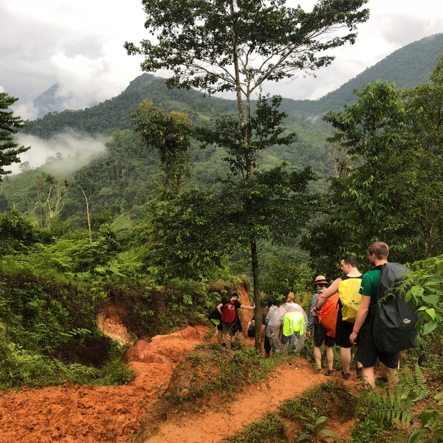 A group of hikers descend an orange dirt path in Colombia's Lost City Trek in the Santa Marta region