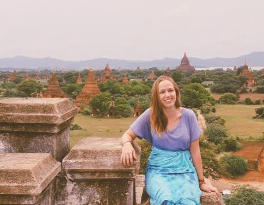 female solo traveler poses for a picture in front of Bagon, Burma