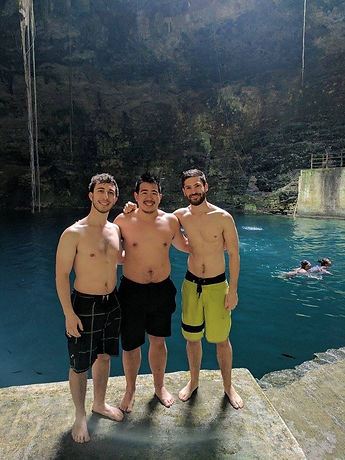 three male travelers posing for a picture in a cenote i Mexico's Yucatan Peninsula