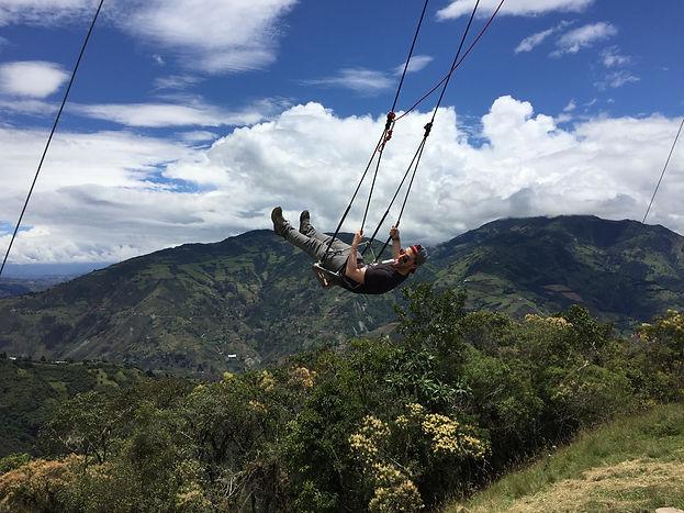 a male traveler on the swing at Casa de Arbol in Banos, Ecuador