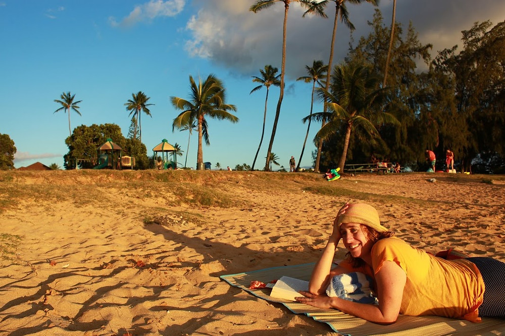 Meredith from Beautiful Voyager posing for a picture on the beach in Kauai Hawaii with palm trees and beautiful sand