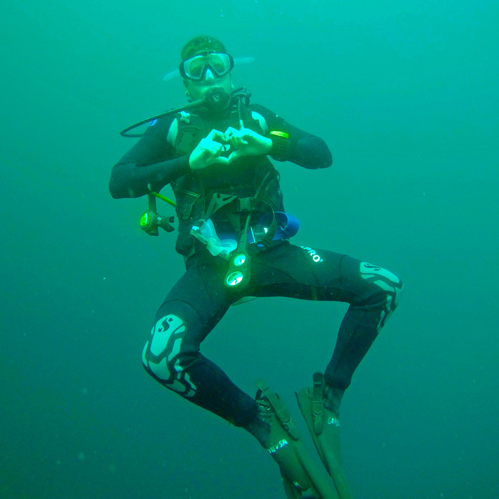 Timm, creator, author and travel blogger of Llama Socks Travel, making a heart with his hands during a scuba diving session undewater