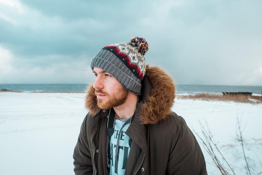 Steven of the Anxious Adventurer poses for a picture in Scotland in winter, wearing a beanie hat and a warm coat