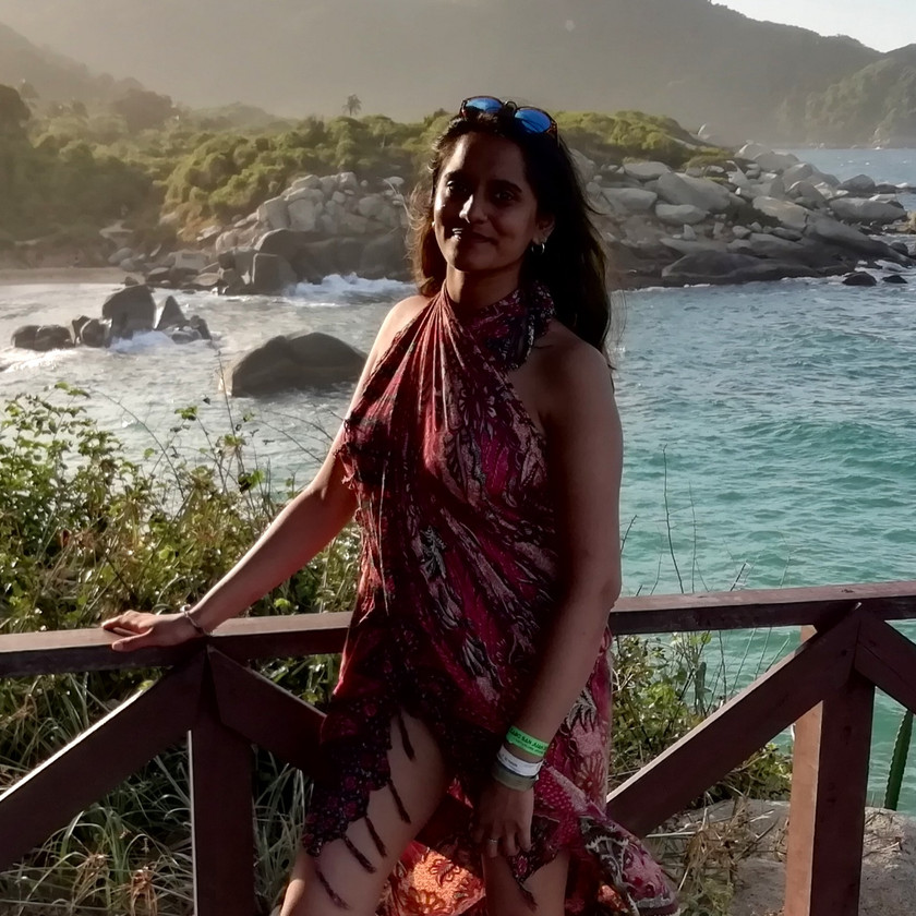 female solo traveler poses in front of a tropical beach