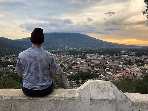 a man sitting at the mirador viewpoint overlooking Antigua Guatemala and Volcan Fuego during sunset