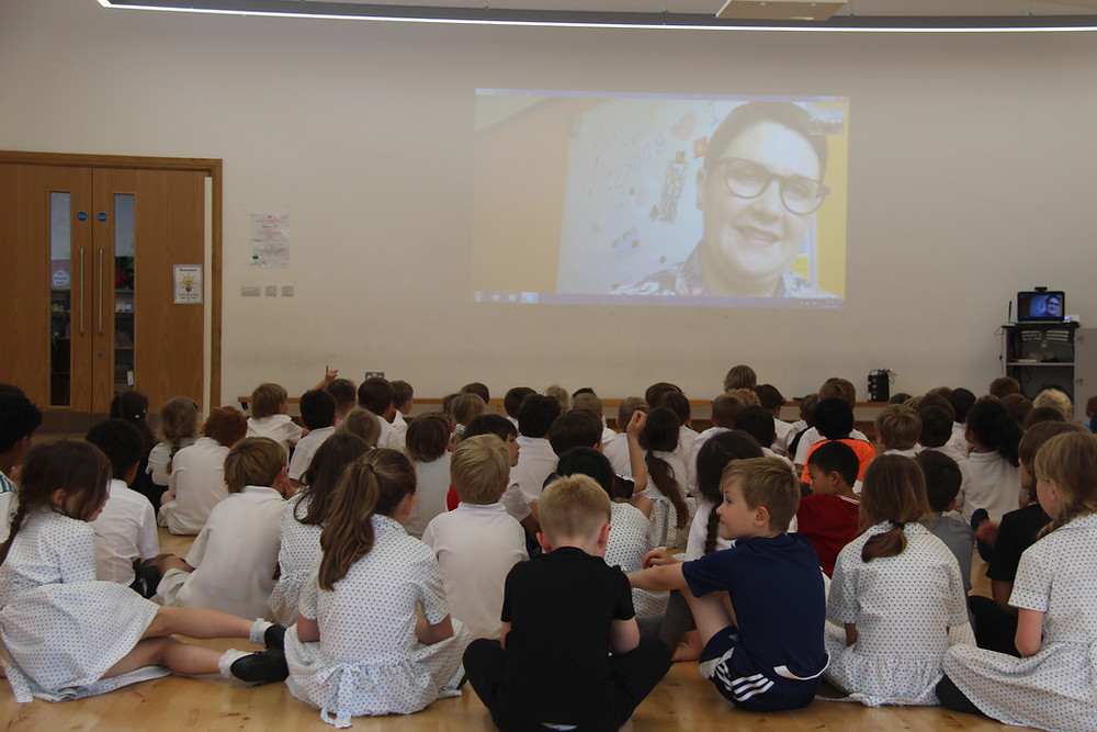 School children watching screen with author talking to them