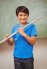 Portrait of cute little boy playing flut