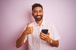 Young indian man using smartphone standi
