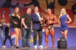 Men's Bodybuildinig Overall Winner Mikhail Volinkin #504 with Arnold Schwarzenegger and Rich Gas