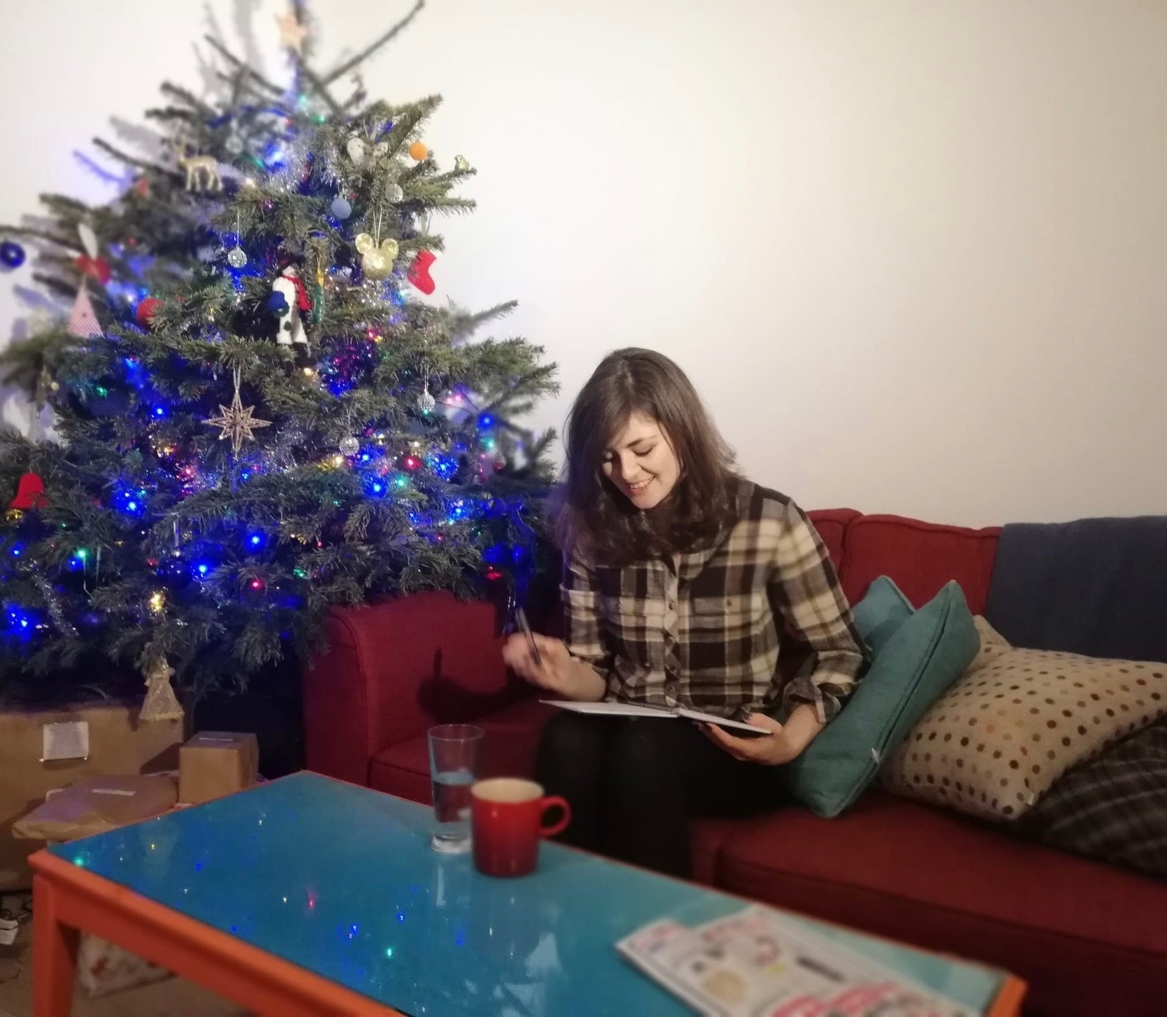 Hannah Duncan female copywriter in a green checked shirt, sitting on a red sofa, with a decorated Christmas tree writing jokes, blue table, red mug