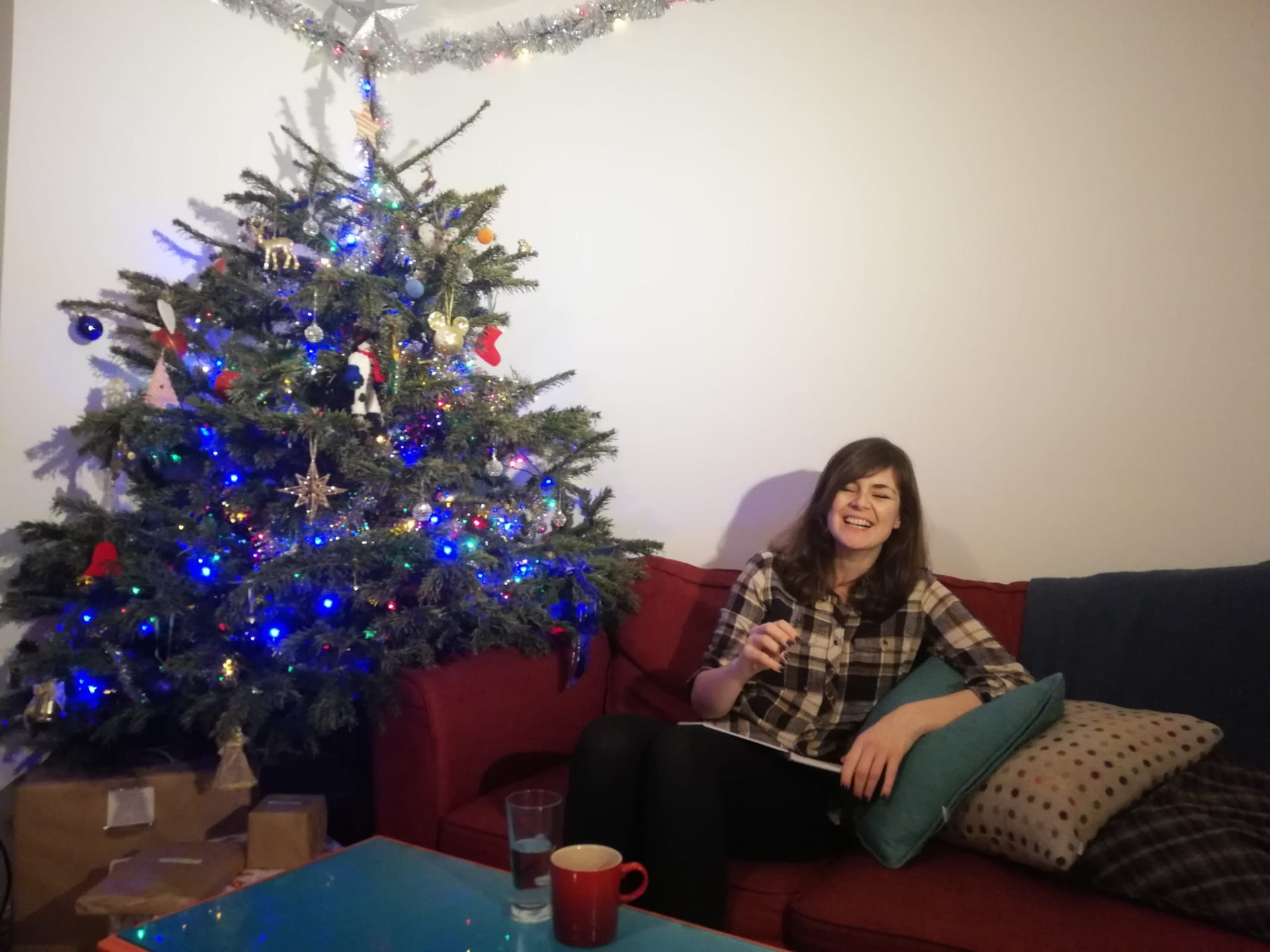 Hannah Duncan, woman laughing on a red sofa next to Christmas tree, writing jokes for SEO Managers, blue table, red mug