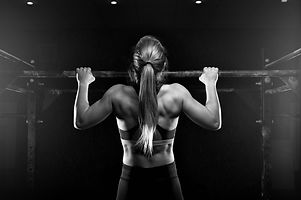 Young muscular woman doing pull up exerc