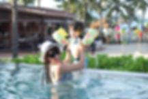 子どもとプールで遊ぶママ