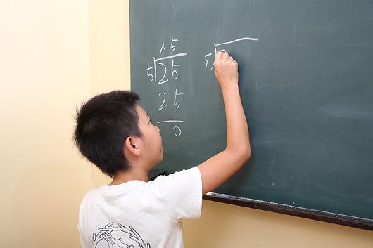 黒板に計算式を書く男の子