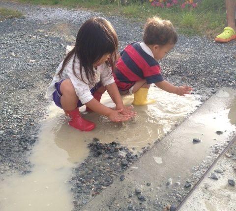 仲良く水たまりで遊ぶ姉弟