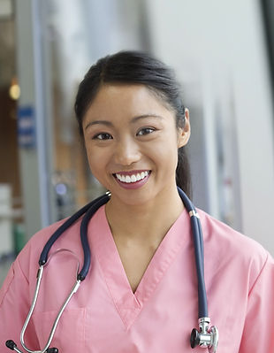 A nurse is smiling at the camera. She is wearing a pink gown, and has a stethoscope around her neck
