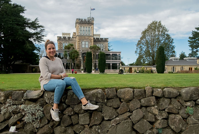 girl-sitting-in-fron-of-Larnach-Castle-with green-grass-in-background