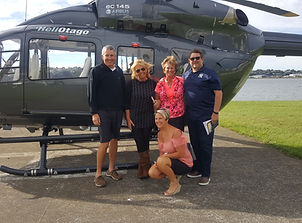 Heli tour guests and guide posing for picture in front of Helicopter