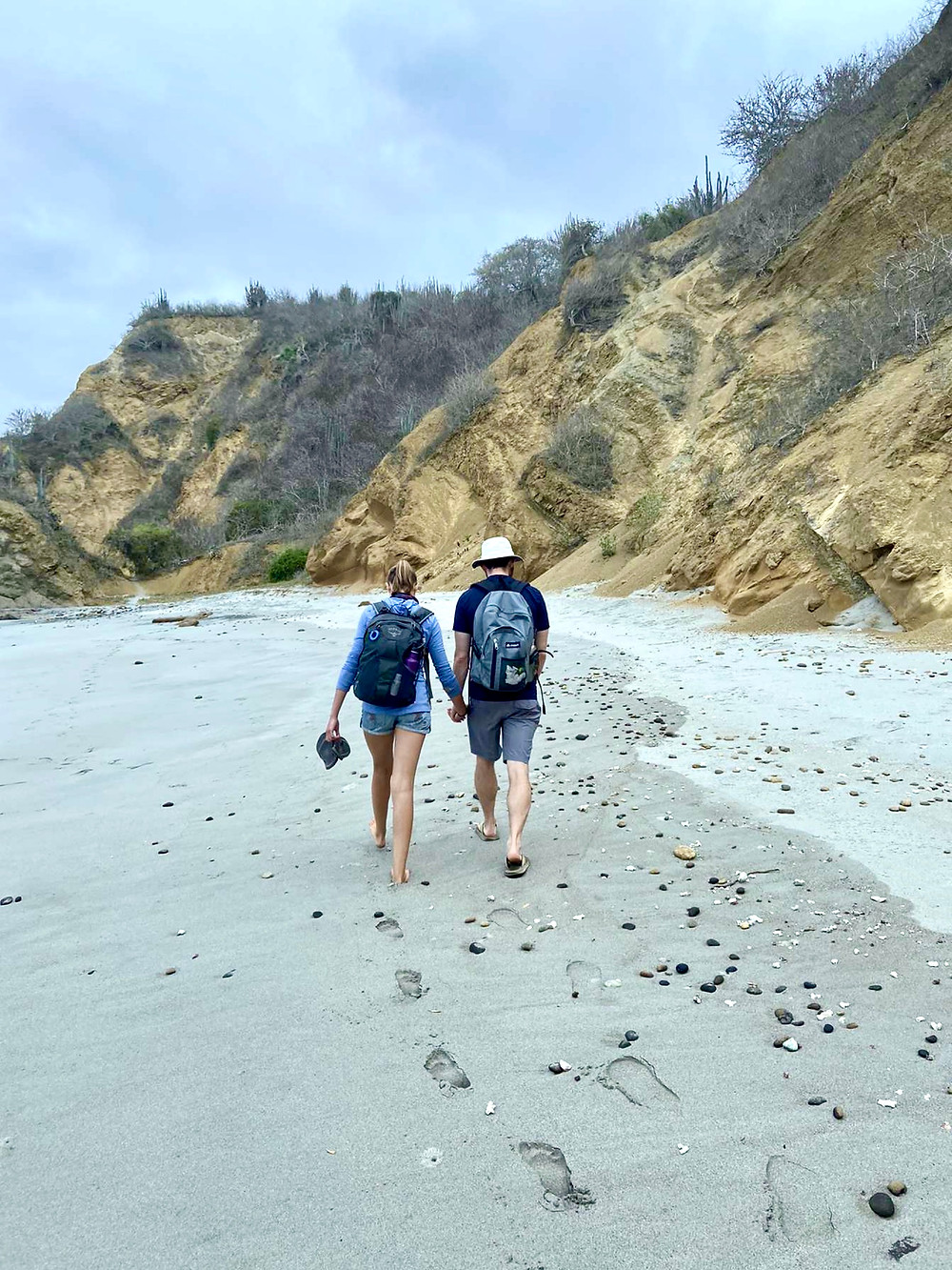 A couple walks with their back to a camera towards a brown sand cliff on a beach.