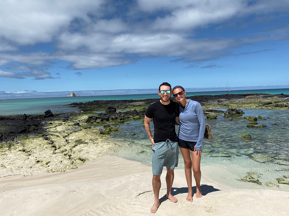 Man and woman pose for a picture on a white sand beach with a crystal blue sea behind them and several low rock formations.