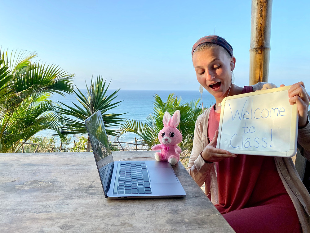 "Girl sits facing her laptop while holding a whiteboard that says ""welcome to class"". She is sitting outside near the ocean with some tropical plants in the background."