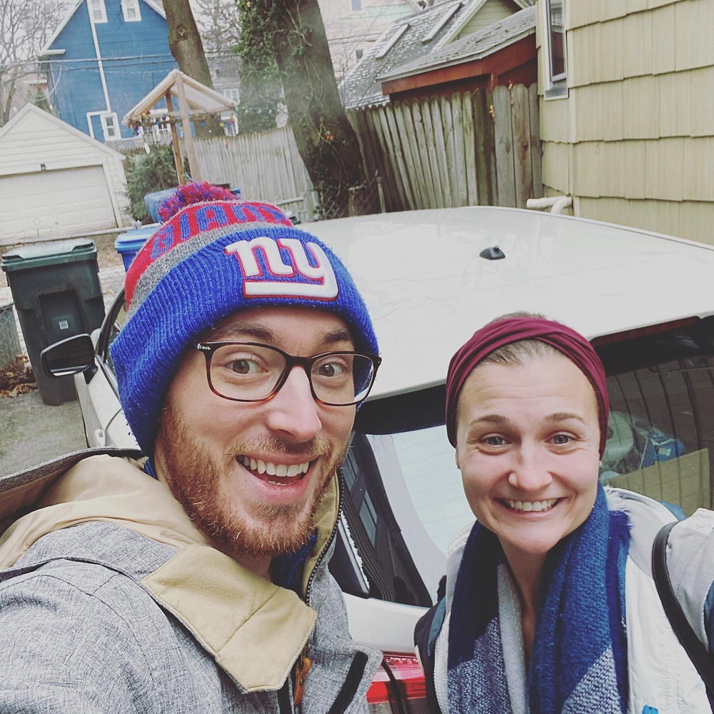 A male and female stand in front of a packed car smiling. The bearded man is wearing glasses and a New York Giants hat and the woman stands next to him with a maroon headband and blue blanket scarf around here neck.