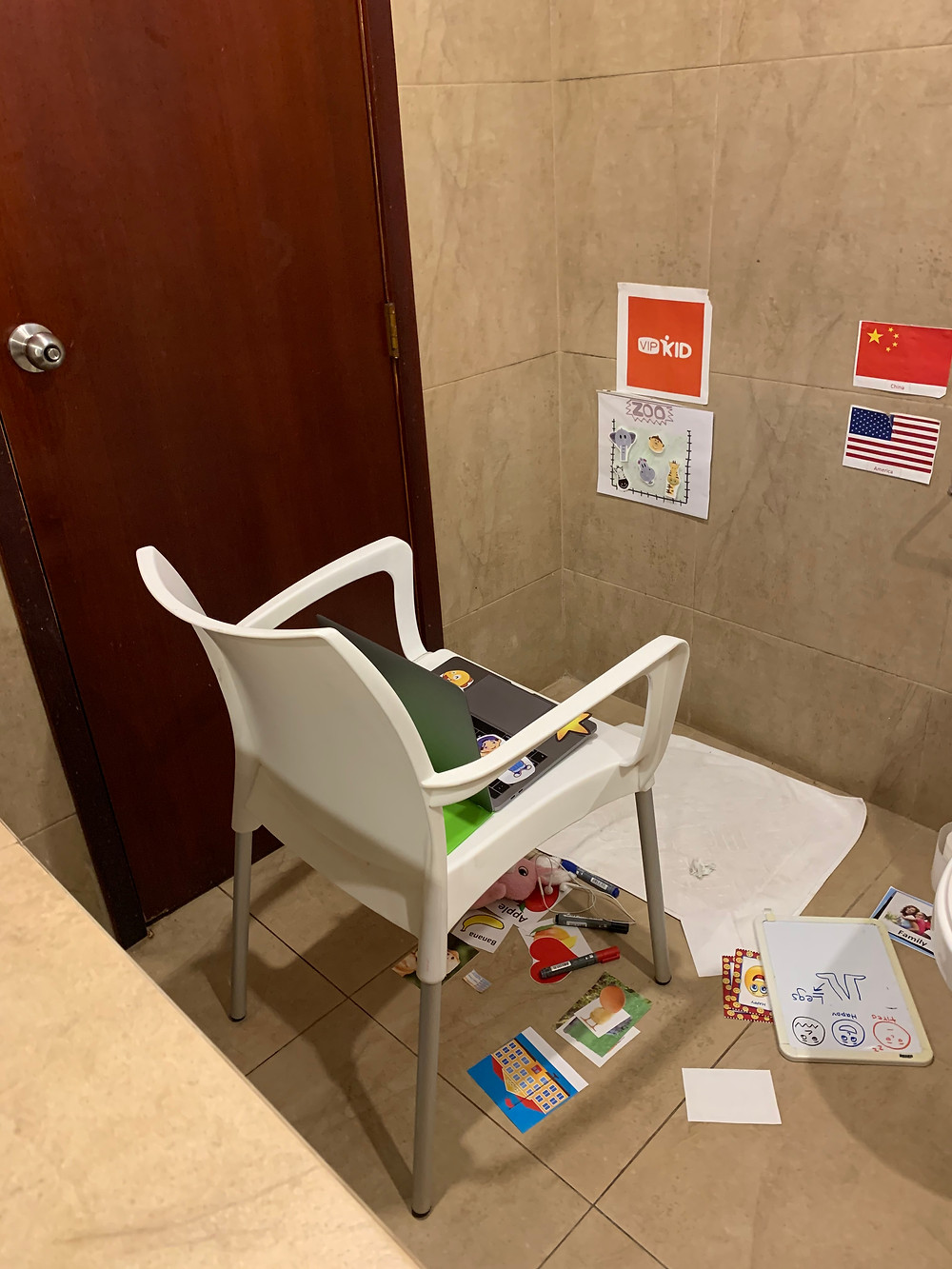 Image of a corner of a small room. A white chair sits in front of a doormat which a computer on it. The wall in front of the chair has 4 wall decorations; a chinese and american flag, a Vipkid sign and an image of animals at the zoo. Surrounding the chair on the floor are an assortment of English flashcards.
