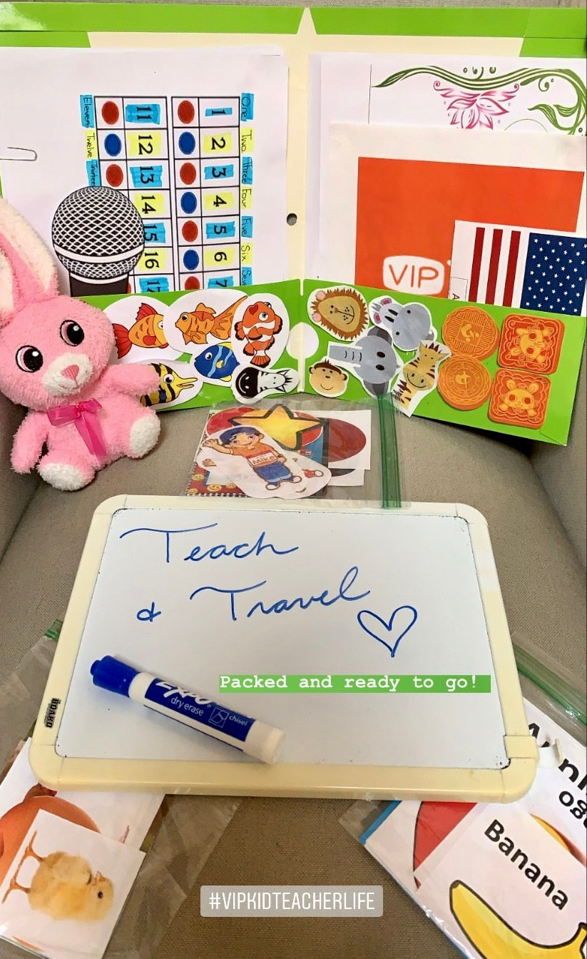 "A bright green folder carrying 2D printable teaching tools. A pink fluffy bunny and white board rest beside the folder. On the white board is written ""teach and travel, packed and ready to go"""