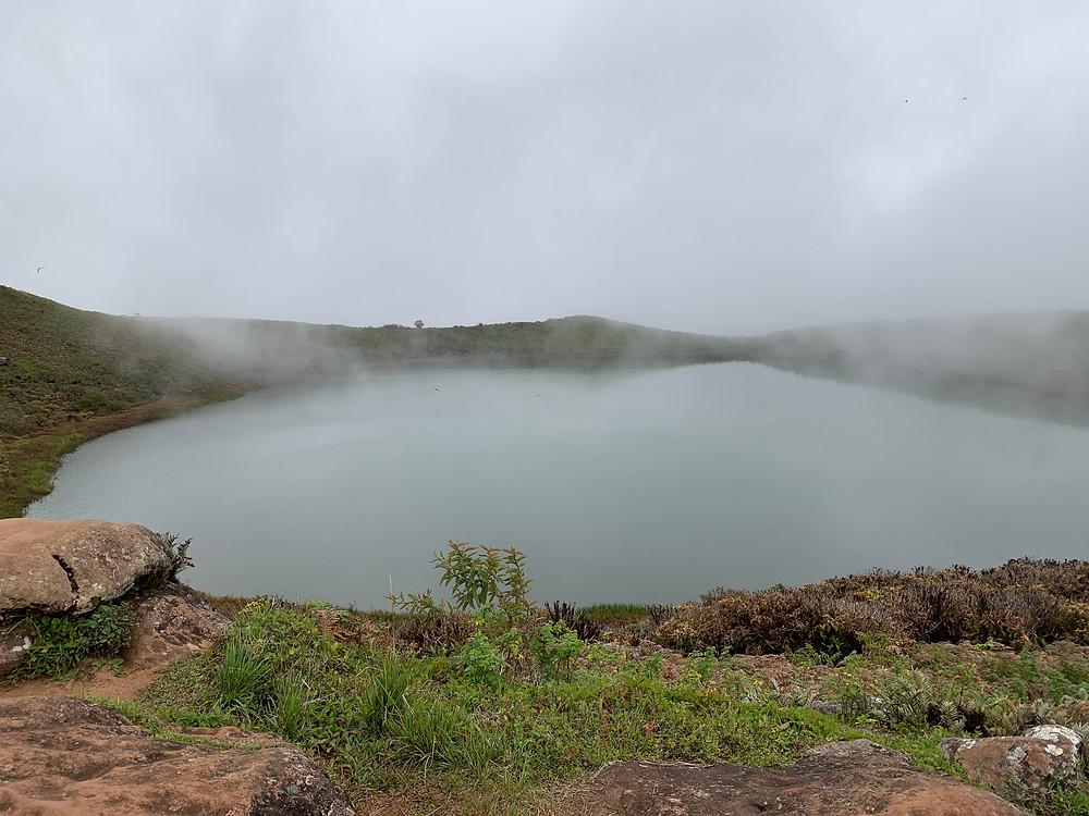 Crater filled with water. Fog descends slightly above the circular crater.