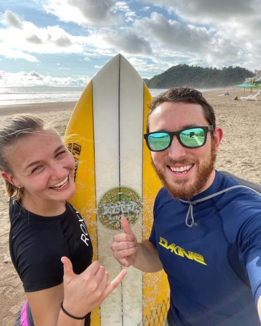 2 people stand in front of a yellow and white surf board smiling and showing the hang lose sign with their hands. A beach is in the background.