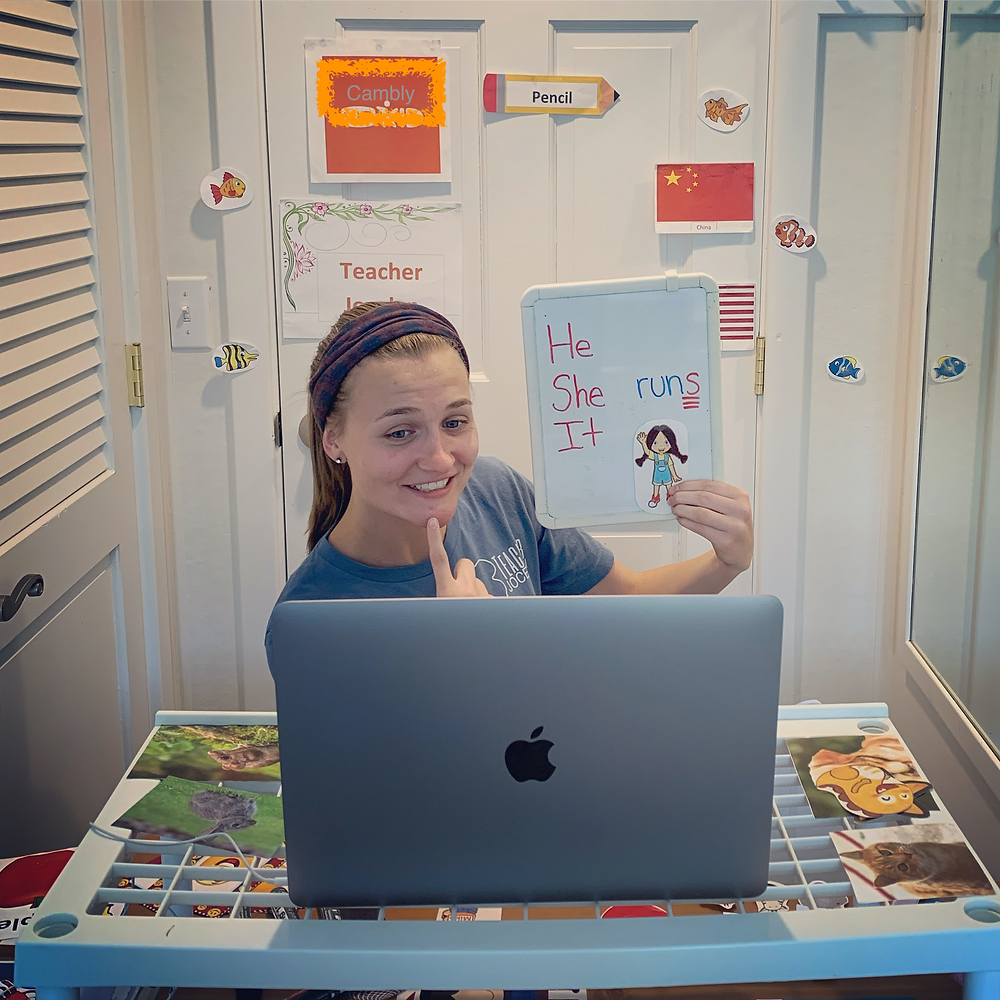 A smiling woman sits in front of a doorway in front of her mac laptop. She is pointing to her lips and is holding a white board that reads He/She/It runs.