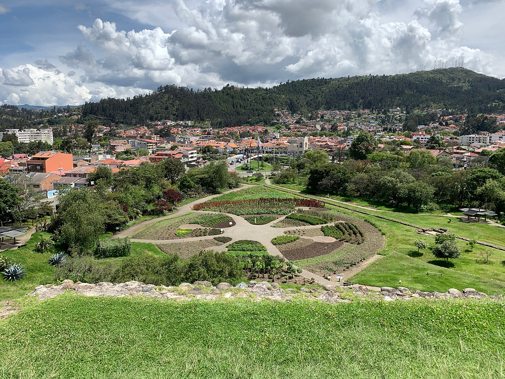 View of an extensive garden with the city behind it. The garden is in the shape of a circle with pathways extending from the center.