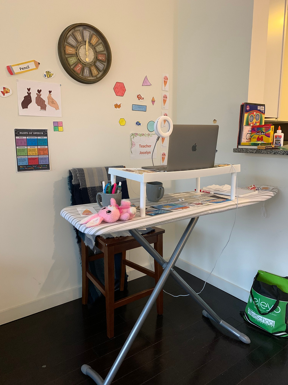 An ironing board is being used as a desk in this image. A white plastic shelf sits on top of the ironing board and holds a mac laptop.