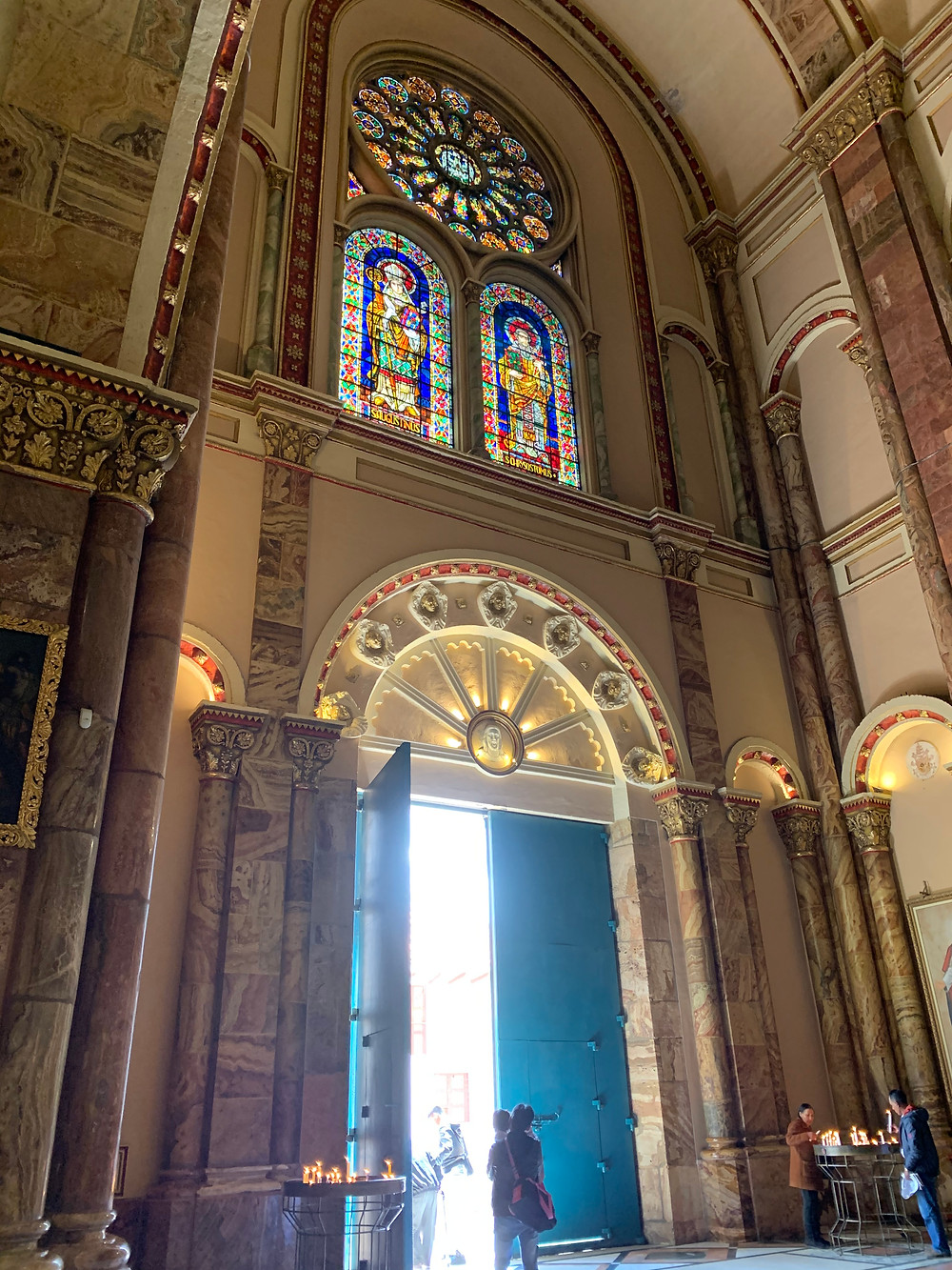 Inside of the Cathedral of Cuenca. A large door stands with one of its doors open with sunlight pouring in. A stainglass window sits near the ceiling with images of the saints and apostles.