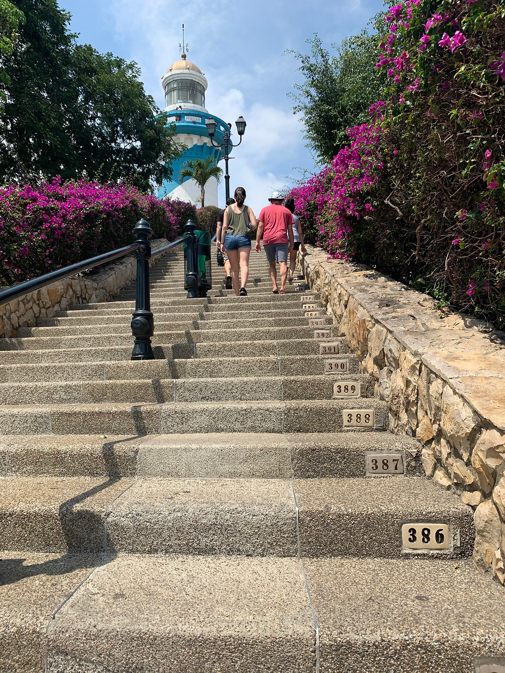 A family of three climb the final numbered steps to a blue and white lighthouse at the top of hill in Guayaquil.