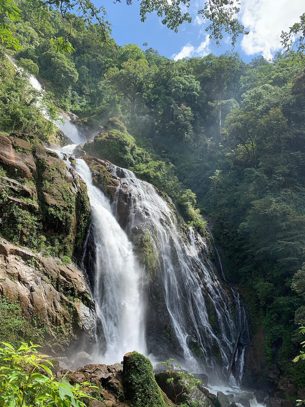 Large waterfall in Costa Rica. Water rushes down the rock face with a powerful force turning the water white. A lush green forest surrounds the falls.