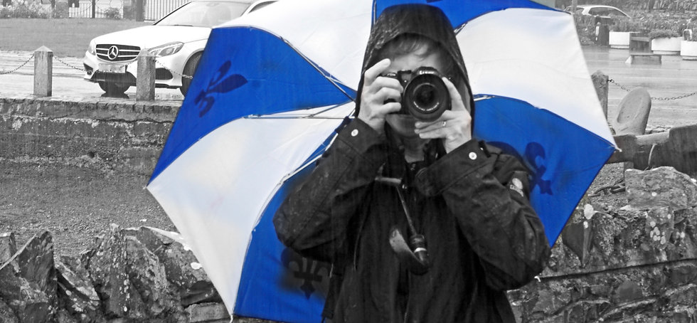 A very wet female photographer takes a photo in heavy rain sheltering under a blue and white umbrella.