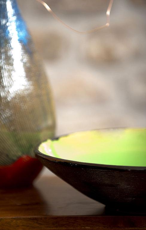 piatto ceramica verde con bordo esterno nero lucido e vaso bottiglia blu bronzo con sfumature di colore