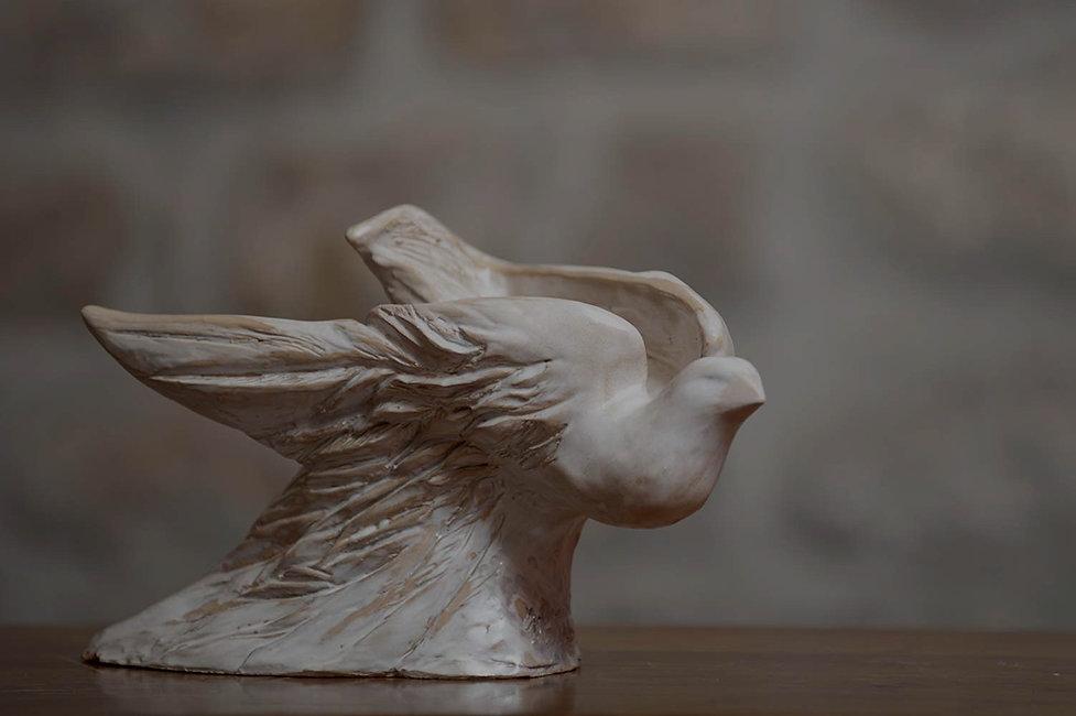Scultura in ceramica di colomba, pronta per spiccare il volo