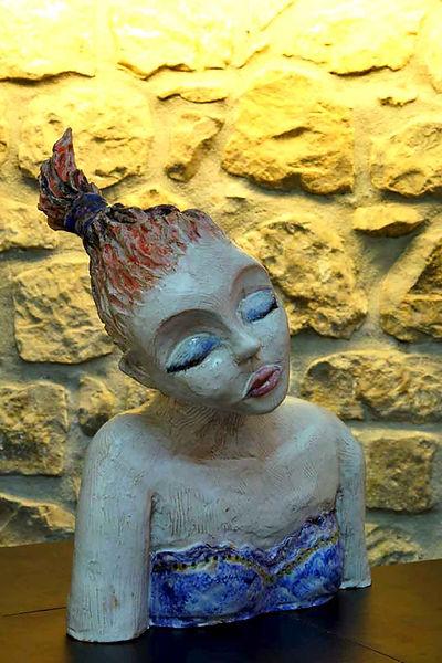 Scultura in ceramica di donna sognatrice con gli occhi chiusi e i capelli rossi raccolti