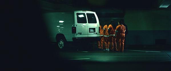 detainees line up to get in a van in und