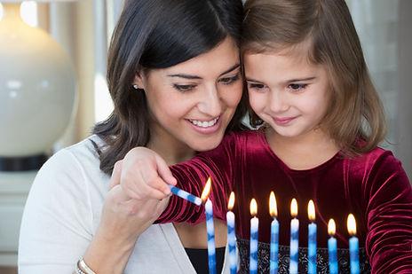 Mãe e filha acendendo velas