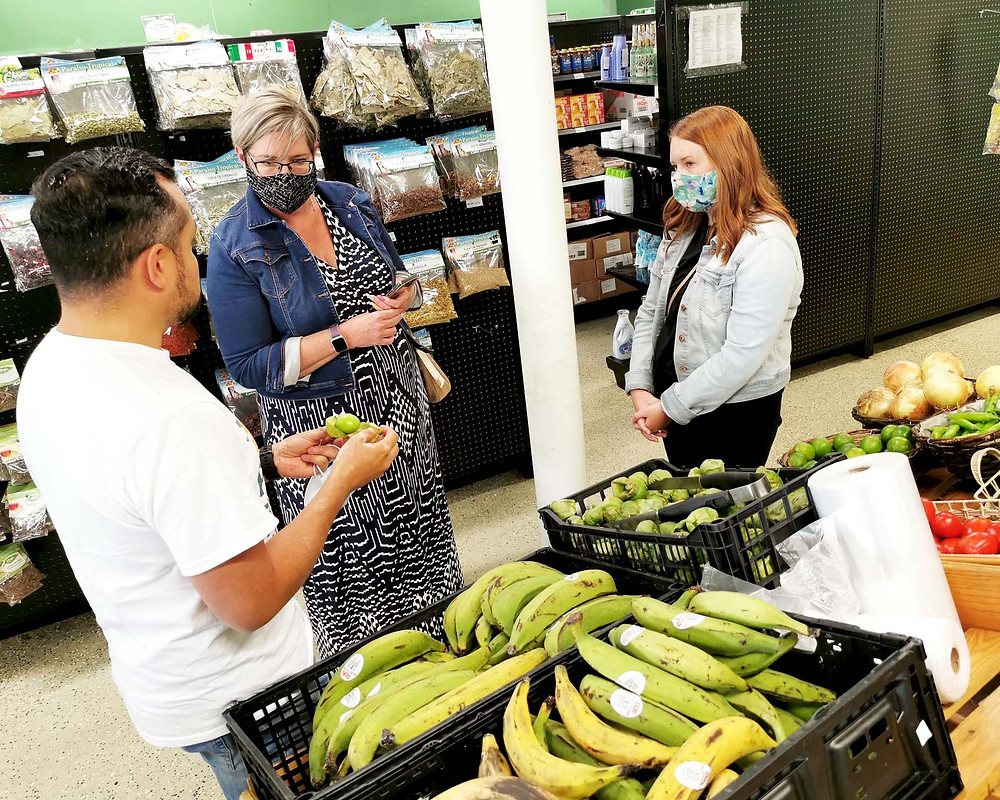 Paraiso Tropical Latin Food Market owner explains what a tomatillo is to visitors