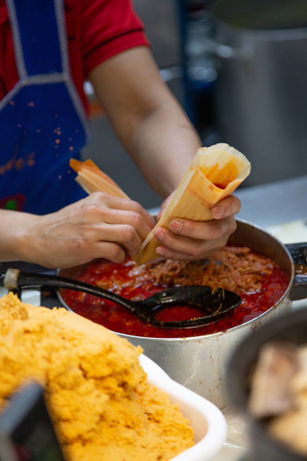 Preparing Mexican tamales with corn husk at Paraiso Tropical.