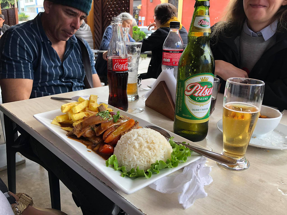 Lomo saltado served with rice & fries at a restaurant in Lima, Peru.