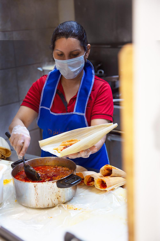 Cook at Paraiso Tropical (north) prepares Mexican tamales.