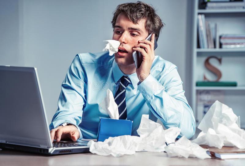 travailleur-malade-avec-les-tissus-de-papier-sur-le-bureau-parlant-au-téléphone-99032126